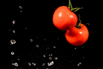 Tomato in spray of water. Water splashing on Fresh Red Tomatoes over black background