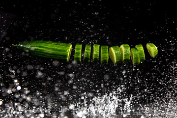 cucumber with splashing water or explosion flying in the air isolated on black background