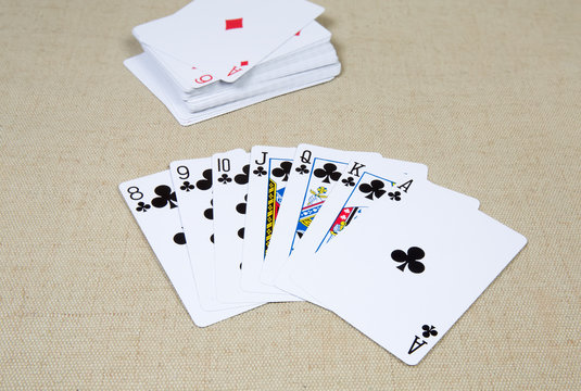 Clubs playing cards laid out against the deck playing cards
