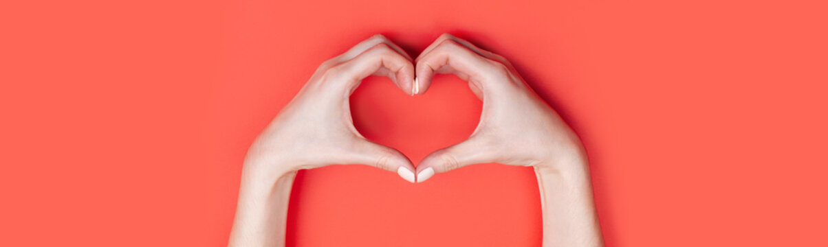 Female hands show a heart symbol on a red background. Place for text, copy space, banner format