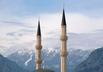 Muslim minarets rise against the backdrop of impregnable snow-capped mountains overgrown with vegetation under serene blue sky Wall mural
