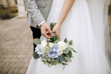 Beautiful wedding bouquet in the hands of the bride and groom Fotobehang
