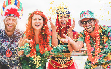 Happy dressed people celebrating at carnival party throwing confetti - Young friends having fun together at fest event - Youth, hangout, festive and happiness concept - Focus on left couple hands Wall mural