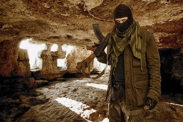 armed masked soldier in a cave. guerrilla warfare.