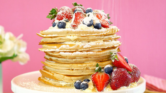 Shrove Pancake Tuesday, last day before Lent, stack of pancakes cake prepared with layers of whipped cream and fresh berries against modern pink background. Close up.