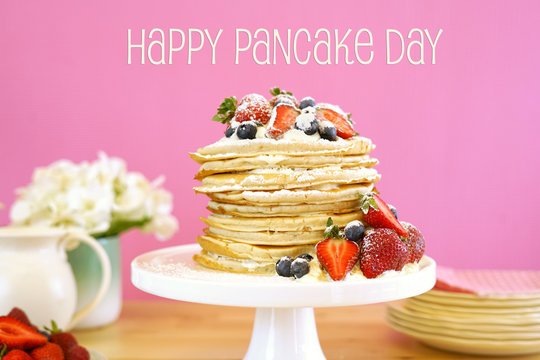 Shrove Pancake Tuesday, last day before Lent, stack of pancakes cake prepared with layers of whipped cream and fresh berries against modern pink background. Happy Pancake Day greeting text message.