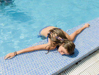 High Angle View Of Teenage Girl Leaning On Retaining Wall While Standing In Pool