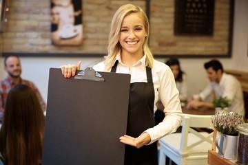 Happy waitress holding blackboard