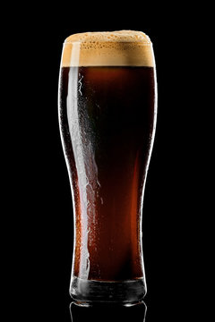 Stange beer glass with black stout covered with drops and froth studio shot on black background.