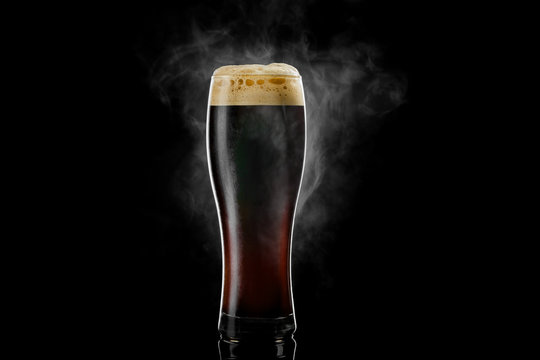 Cold pilsner beer glass with black porter beer inside covered with drops and froth evaporating on black background.