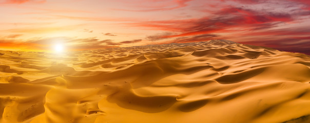 Panoramic view of sunset over the sand dunes in the desert.