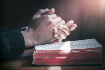 Close up beside of holy Bible with hands praying background, Christian concept.