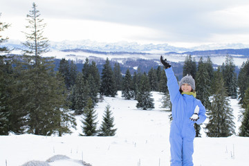 beautiful winter landscape with happy child saying hello to vacation