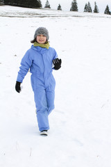 Happy beautiful child walking over snowy mountain, real life nature