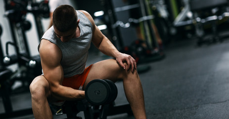 Fit man in sportswear focused on exercise for biceps in the gym