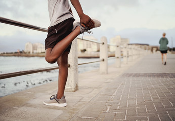 Photo sur Aluminium Jogging Low section of a male sportsman standing near the railing stretching his leg before jogging on the seaside promenade