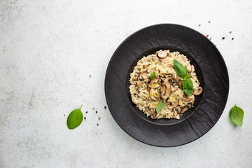 Risotto with mushrooms in a black plate over white background, top view Wall mural