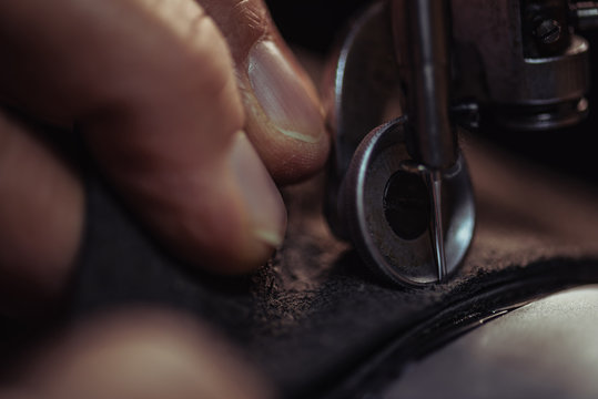 close up view of cobbler sewing genuine leather on sewing machine