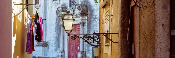 Straatlantaarn en wasgoed in een pittoresk smal straatje van Alfama in het oude centrum van Lissabon, Portugal