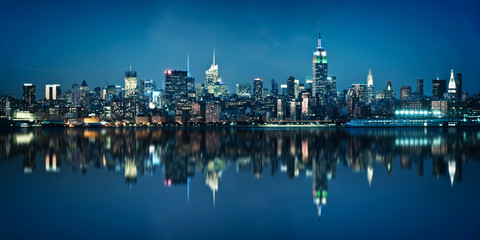 Panorama of the skyline of Manhattan viewed from Jersey city during the blue hour. New York skyline at night with reflections.