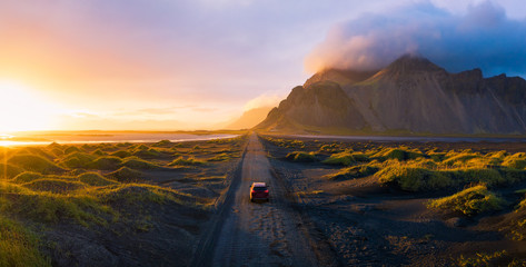 Foto op Plexiglas Zwart Gravel road at sunset with Vestrahorn mountain and a car driving, Iceland