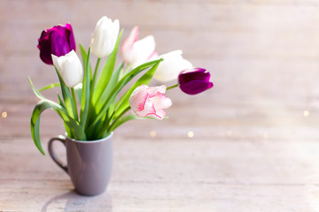 Fotomurales - Tulips at wooden background. Spring flowers in gray cup. Bouquet in vase. Pink, white, lilac and purple blooming flora in sunshine. Cozy still life. Copy space.