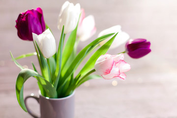 Fotomurales - Tulips at wooden background. Spring blooming flowers in gray cup. Bouquet in vase. Pink, white, lilac and purple flora in sunshine. Close up.