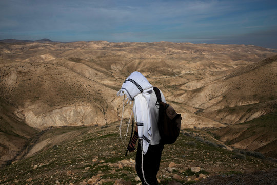 A Jewish shepherd wears a prayer shawl as he stands in the landscape in the Israeli settlement of Mitzpe Yericho in the Jordan Valley in the Israeli-occupied West Bank