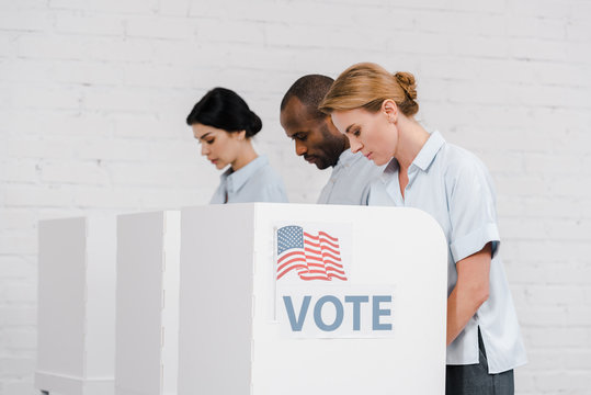 side view of women and african american man voting near vote lettering and brick wall