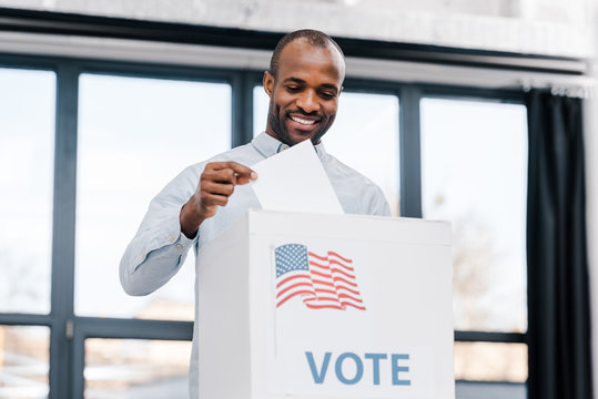 happy african american man voting and putting ballot in box with flag of america