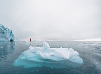 Beautiful red sailboat in the arctic next to a massive iceberg showing the scale. Cruising among...