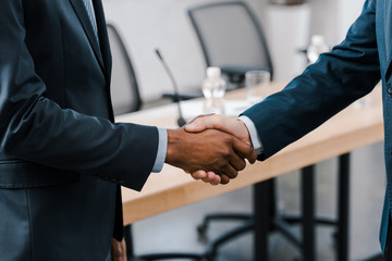 cropped view of businessman shaking hands with african american diplomat