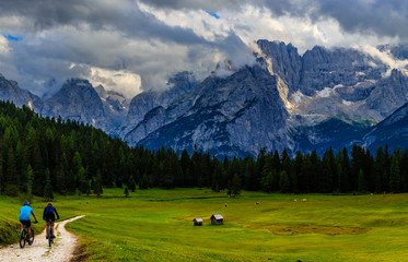 Couple cycling in Cortina d'Ampezzo, stunning Dolomites mountains in background. Woman and man riding MTB trail. South Tyrol province of Italy, Dolomites.