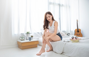 Portrait of beauty  smiling asian woman applying a lotion to her leg skin during her morning routine. Cute asian girl. Skincare body lotion, beauty clinic skincare spa indoors woman lifestyle concept
