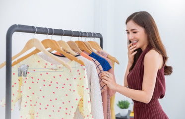Portrait of happy young beautiful asian girl choosing cloths in shopping mall or clothing store on sale. Woman lifestyle sale, fashion, consumerism people and Black Friday shopaholic concept