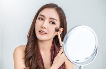 Closeup portrait of young beautiful asian girl  apply brush on mirror makeup routine with copy space. Beauty woman with perfect glow skin dress up. Healthcare woman lifestyle cosmetic concept