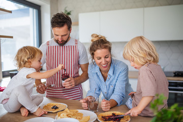 Photo sur Aluminium Pain Young family with two small children indoors in kitchen, eating pancakes.