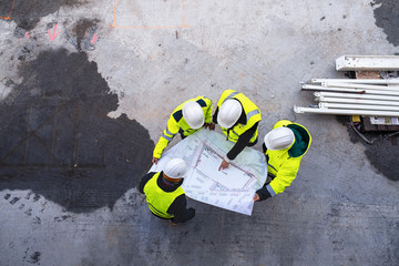 A top view of group of engineers with blueprints standing on construction site.