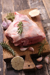 raw lamb leg with rosemary on wooden board