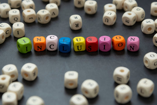 Inclusion text of multi colored cubes on dark background. Inclusive social concept.