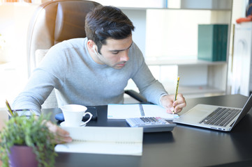 A young man working at a desk with a laptop. Calculator, notepad, pencil, pen and cup of coffee on the side.