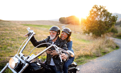 In de dag Hoogte schaal Cheerful senior couple travellers with motorbike in countryside at sunset.