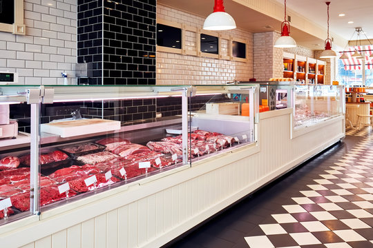 Selection of raw fresh veal meat in the refrigerated display of a butcher shop