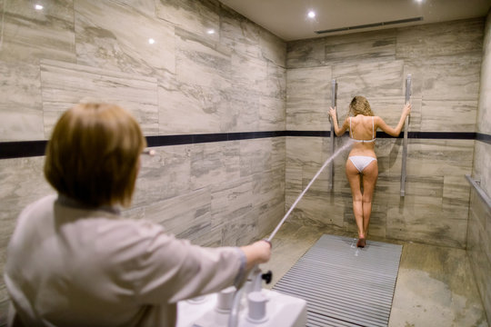 Young blond woman in white swimsuit having high pressure massage with Charcot shower for anti-cellulite treatment in the spa salon