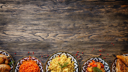 Eastern cuisine. Homemade Uzbek dishes, pilaf, chicken, samsa, Korean carrot salad on a wooden background. baner background image, copy space text, top view