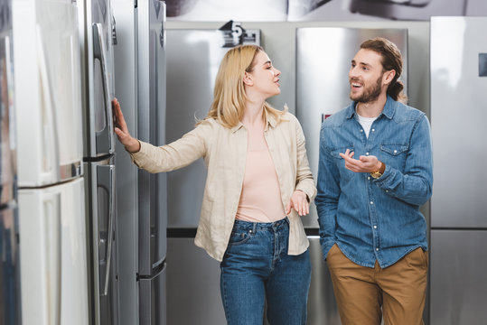 smiling boyfriend pointing with hand and girlfriend touching fridge in home appliance store