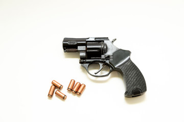 black revolver pistol with cartridges on a white background