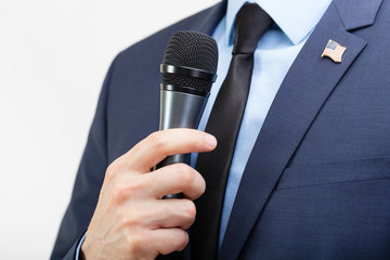 Man in suit with tie and USA flag pin on chest holding microphone