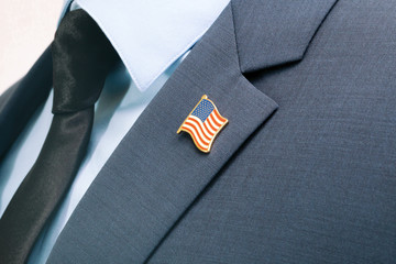 Man in suit with tie and USA flag pin on chest