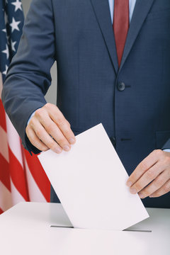 Caucasian male in suit holding ballot paper in hand and throwing it into election box with USA flag on background - studio shot